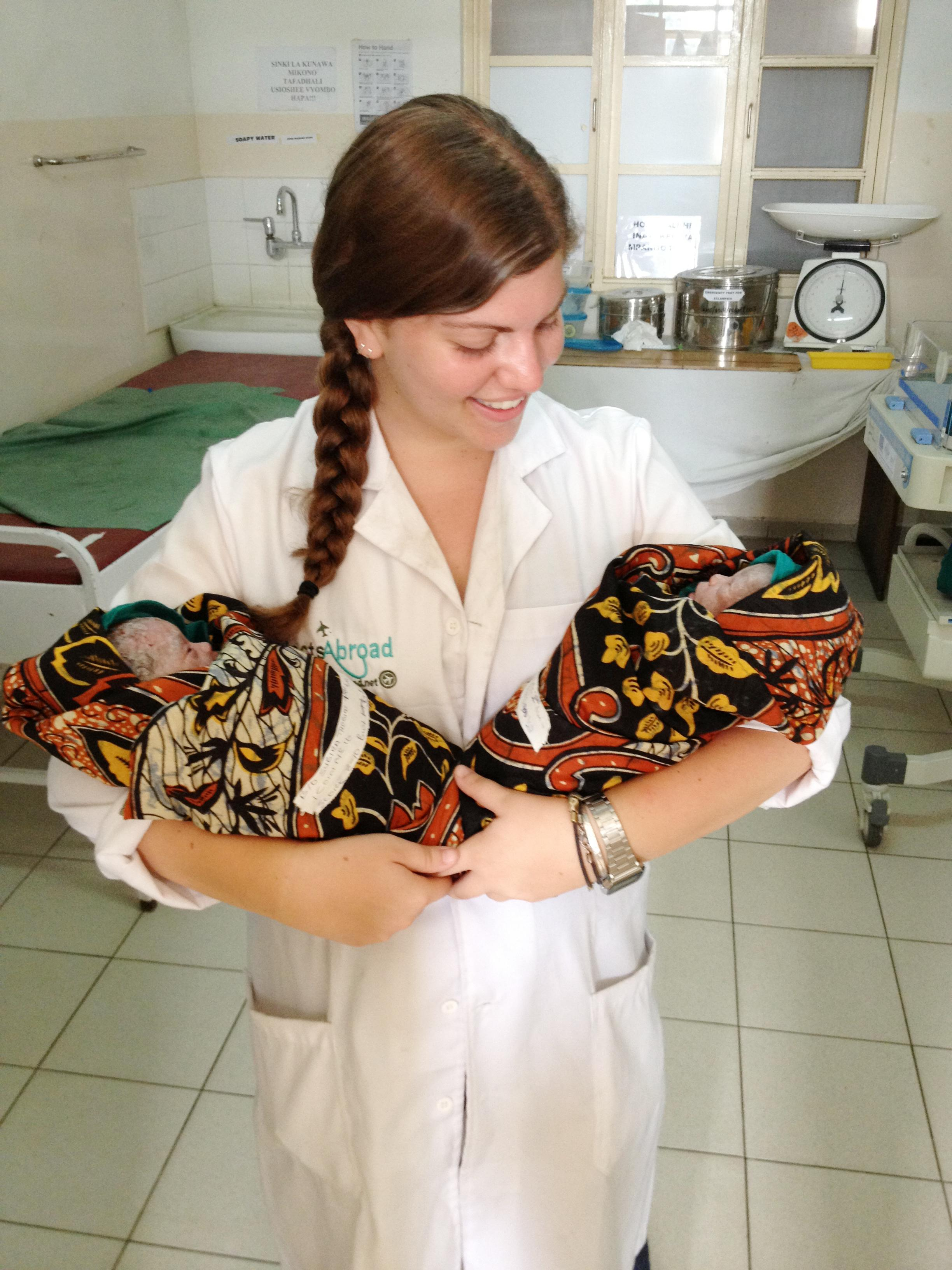 An intern photographed holding newly born twins whilst on her midwifery internship in Tanzania with Projects Abroad.
